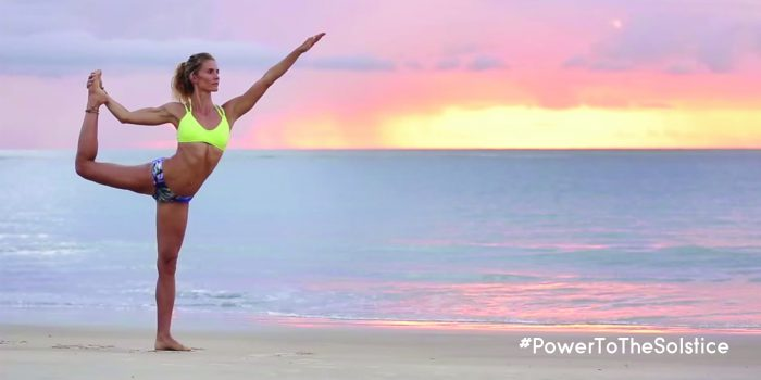 Woman doing yoga on the beach with notation #powertothesolstice. Athleta